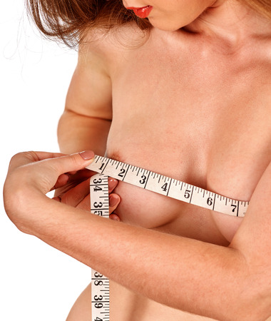 beauty breast: Girl measures her nude breast measuring tape. Isolated. Stock Photo