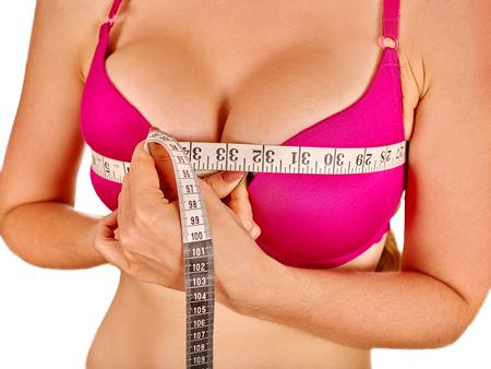 senos: La muchacha que desgasta en ropa interior roja mide su cinta métrica de mama. Aislado.