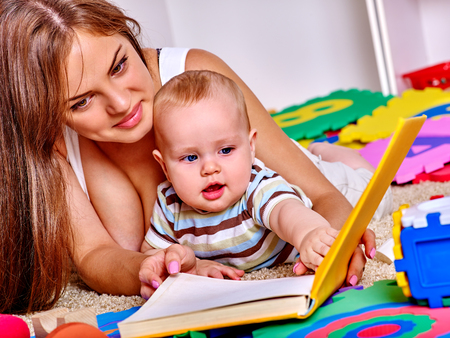 mothers group: Kid baby boy with mother  lying on floor and plying with puzzle toy at home.