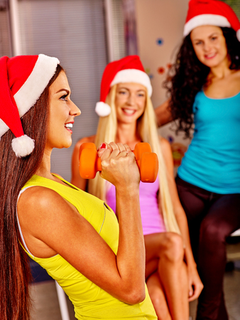 gym clothes: Girls in Santa hat holding dumbbells in sport gym. Sport Christmas concept Stock Photo
