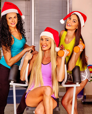 gym clothes: Young woman wearing santa hat  holding dumbbells in sport gym. Sport Christmas concept Stock Photo