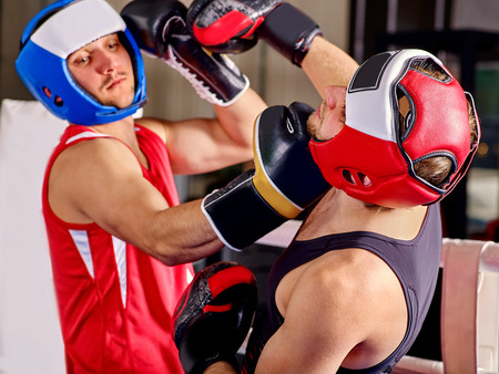 kick boxing: Two  men boxer wearing helmet and  gloves boxing . Uppercut. Stock Photo