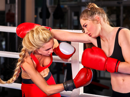 arena: Two  women boxer wearing red  gloves to box in ring work sport reception