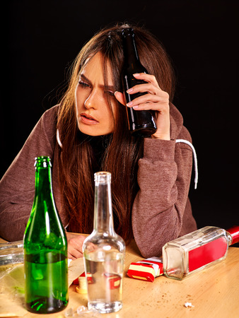 drunk girl: Drunk girl holding bottle of alcohol. Mess on table. Soccial issue alcoholism.