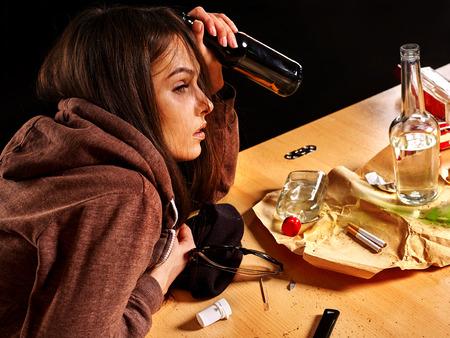 alcoholismo: Muchacha borracha con una botella de alcohol. Alcoholismo tema Soccial. Vista lateral. Foto de archivo