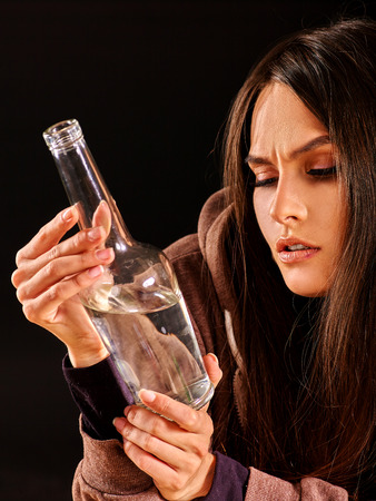 drunk girl: Drunk girl looking at bottle of alcohol. Soccial issue alcoholism. Stock Photo