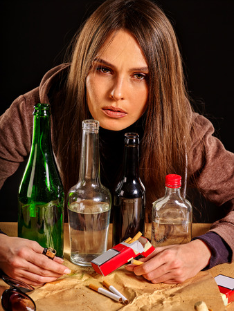 drunk girl: Drunk girl covers group bottles of alcohol. Soccial issue alcoholism. Stock Photo