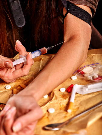 tourniquet: Female drug addict with  tourniquet does intravenously intravenous injection on his arm and  syringe.