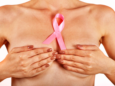 senos: Pink badge on woman hand cover breast  to support breast cancer cause. Social awareness symbol. Foto de archivo