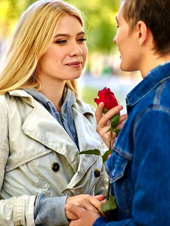 girl portrait: Young couple hugging and flirting in  park  and looking away. Man present rose by woman