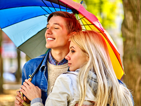 love in rain: Happy young couple embracing under umbrella in autumn day. Side view.