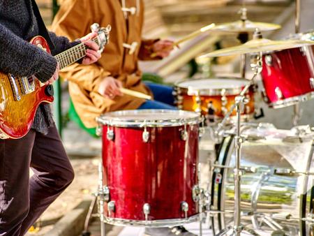tambor: Manos con el bombo de los actores masculinos de la calle que juegan música percusiones en otoño al aire libre.