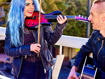 street party: Music street performers  with happy smiling girl violinist and man guitarist on blue sky outdoor. Stock Photo