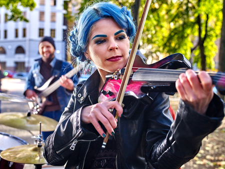 performers: Music street performers girl violinist with blue hair playing  in city park  outdoor. Stock Photo