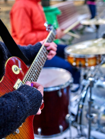improvisation: Music street performers on autumn outdoor. Middle section of body part. Hands with guitar on foreground. Stock Photo