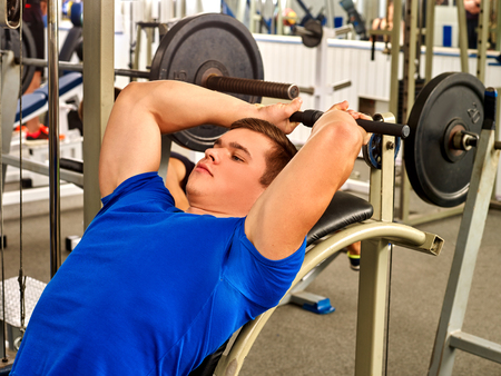male athlete: Man lying on bench working his arms and back at gym. He lying on bench and lifting barbell. Stock Photo