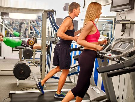 treadmill: Man and women running on treadmil at gym.