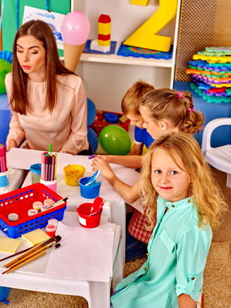 children drawing: Children with young woman painting on paper at table  in  kindergarten .