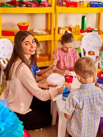 kinder: Los ni�os con la mujer del profesor de pintura sobre papel a la mesa en el jard�n de infantes. Mirando en la c�mara. Foto de archivo