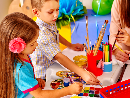 kinder: Los niños con la mujer del profesor de la pintura en el papel en la mesa en el jardín de infantes. Dos niños y un adulto.