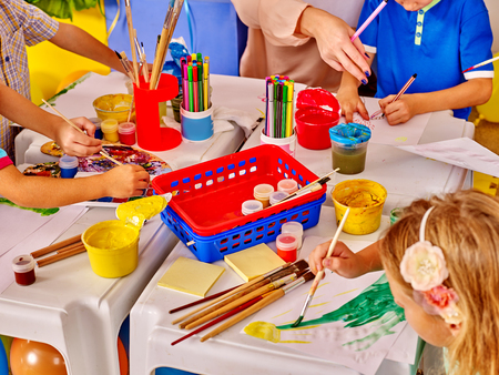 childish: Group kids hands  with brush painting on table in  kindergarten . Top view.