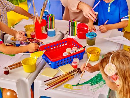 muebles de madera: Los niños del grupo manos con la pintura del cepillo en la mesa en el jardín de infantes. Vista superior. Foto de archivo