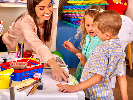 educator: Children small group  with teacher woman painting on paper at table  in  kindergarten .
