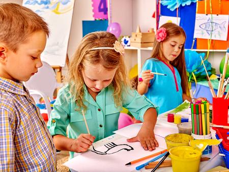 여성과 한 남성 .Two 유치원에서 테이블에 브러시 그림과 함께 그룹 소녀.