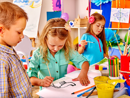 Group little girl with brush painting on table in  kindergarten .Two female and one male.
