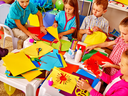 children art: Large Group kids holding colored paper on table in kindergarten .