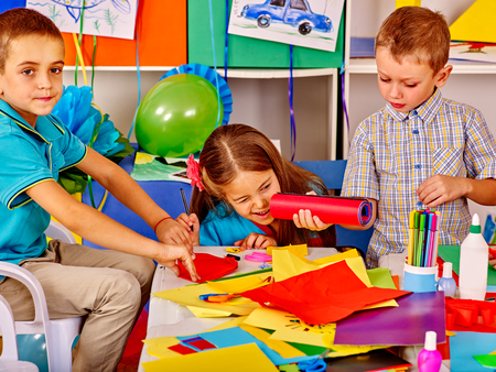 room decor: Group kids holding colored paper on table in kindergarten . Two male.