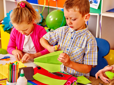 crayon  scissors: Group kids make  paper origami on table in kindergarten .
