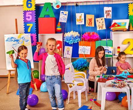 children art: Group kids holding colored paper on table in kindergarten interior.