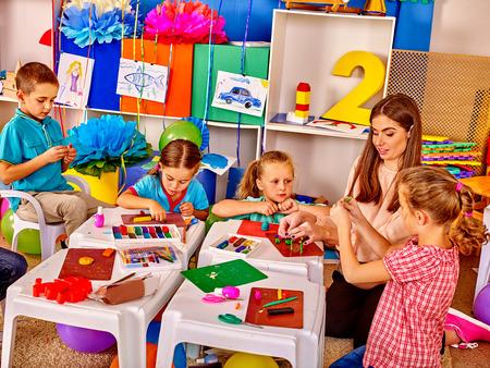 kinder: Ni�os amable Grupo esculpen por plastilina sobre la mesa en el jard�n de infantes. Foto de archivo