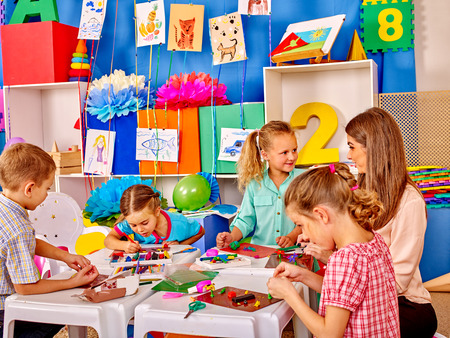 kinder: Lasrge Grupo belleza ni�os esculpen por plastilina sobre la mesa en el jard�n de infantes. Foto de archivo