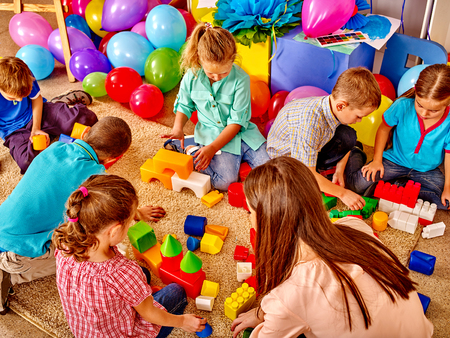 Group children game blocks and balloons on floor in kindergarten . Top view.