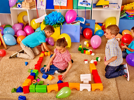 preescolar: Grupo de niños masculinos y femeninos bloques del juego en el piso en el jardín de infantes. Vista superior. Foto de archivo