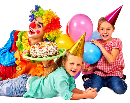 children birthday: Clown holding cake on birthday with two female children. Isolated.