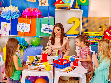 preescolar: Los niños con la mujer del profesor de pintura sobre papel a la mesa en el jardín de infantes de preescolar.
