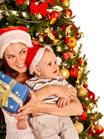 blue gift box: Mom wearing Santa hat holding  baby with blue gift box  under Christmas tree on isolated.