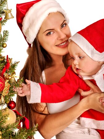 wearing santa hat: Mom wearing Santa hat holding  baby decorating Christmas tree.