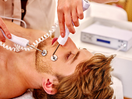 sound therapist: Portrait of man receiving electric facial peeling hydradermie at beauty salon. Indoor