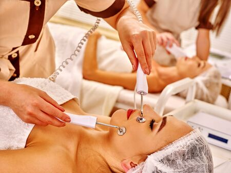 sound therapist: Group young women receiving electric facial massage at beauty salon. Close up. Stock Photo