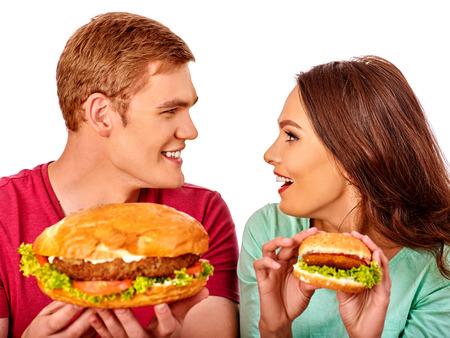 personas comiendo: Hombre joven pareja y la mujer comer hamburguesas grandes y pequeños. Concepto de la comida rápida. Aislado. Foto de archivo