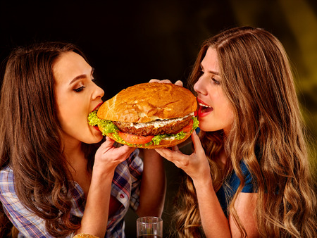 junks: Girl holding and bite big hamburger from different sides. Fastfood concept. Cheeseburger on foreground.