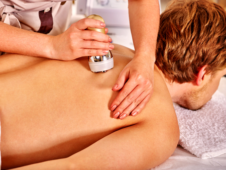peel: Man receiving electroporation back therapy at beauty salon.