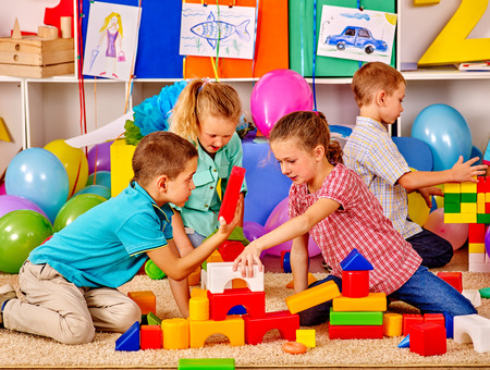 Group children build blocks on floor in kindergarten . Stock Photo