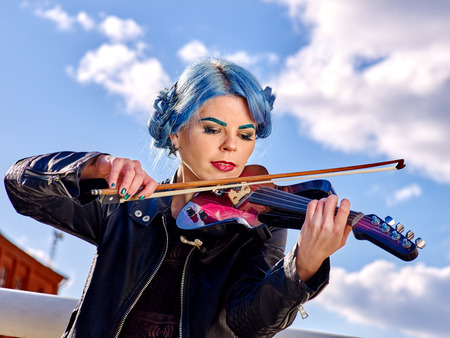 solitariness: Music street performers girl violinist with blue hair and eyebrow playing  aganist sky with clouds outdoor.