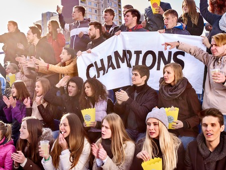 Sport fans in warm clothers holding champion banner  and singing on tribunes. Group people.