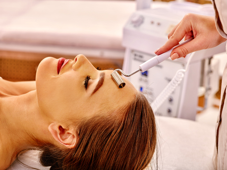 Young woman receiving electric galvanic face spa massage at beauty salon.
